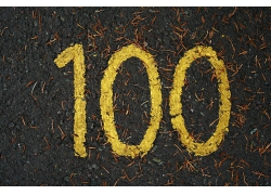 俯拍潮湿地面的黄色数字100