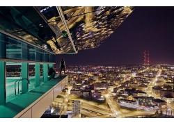 站在高樓陽臺上看城市夜景的人