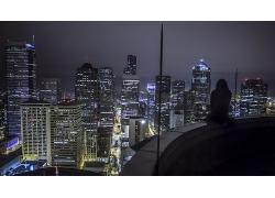坐在高樓陽臺上看城市夜景的女性