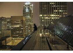 坐在城市高樓天臺上看夜景的女性