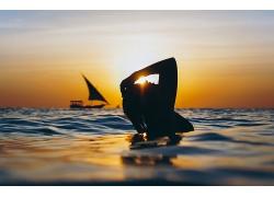 黃昏海里游泳的女性剪影