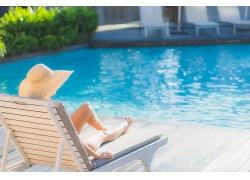 躺在沙灘椅泳池邊的女性