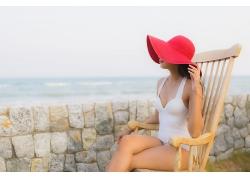 坐在木椅觀看大海的女性