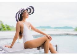 休閑海邊泳池坐著休息的女性